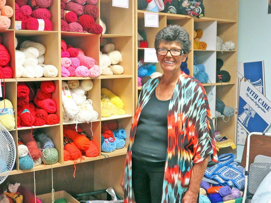 Holli Calder-Cox, Director of Project Warm Up stands in front of yarn supplies