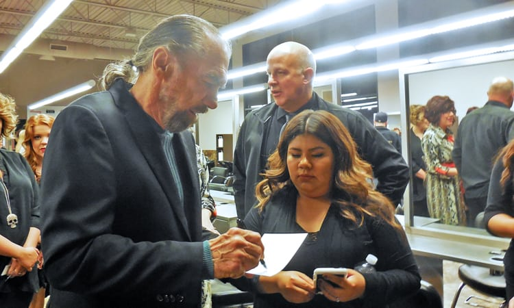 John Paul Dejoria, co-founder and CEO of Paul Mitchell autographs a workbook.