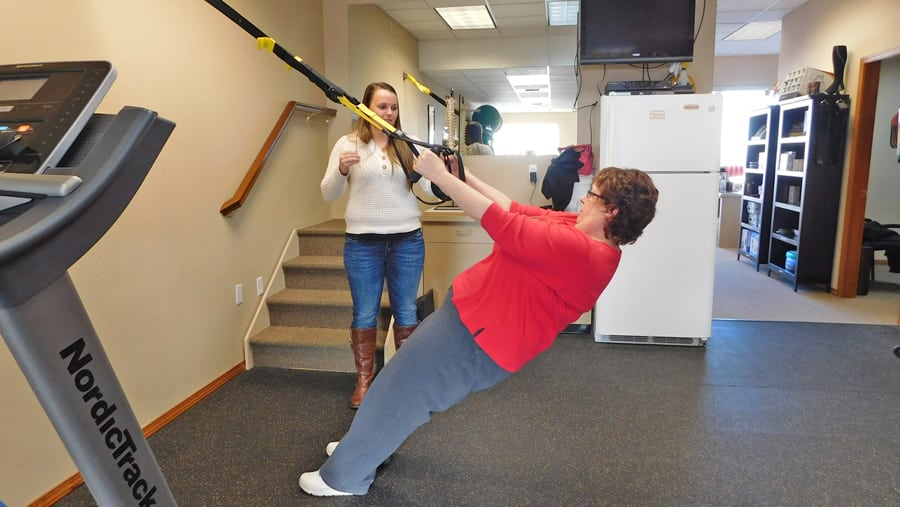 Glenda Higgins of Kennewick works out on a TRX machine, which uses a person's body weight to build muscle strength.