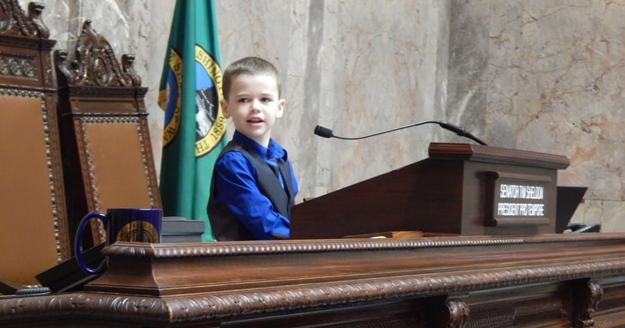 Luke Lynch, 7, of Moses Lake, plays Feb. 24 at the podium of the state Senate after a memorial resolution was read honoring his father, Kyle Lynch, who died of cancer in November. Kyle Lynch was an aide for two 13th District senators from 2003-16. (Courtesy Rebecca White of Columbia Basin Herald)
