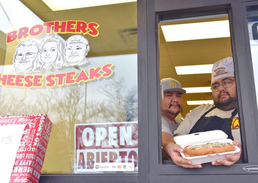 Mario and Coco Quintero pose with their popular Philly cheesesteak sandwich outside in the walk-up window at the Pasco Specialty Kitchen in downtown Pasco at 110 S. Fourth Ave.