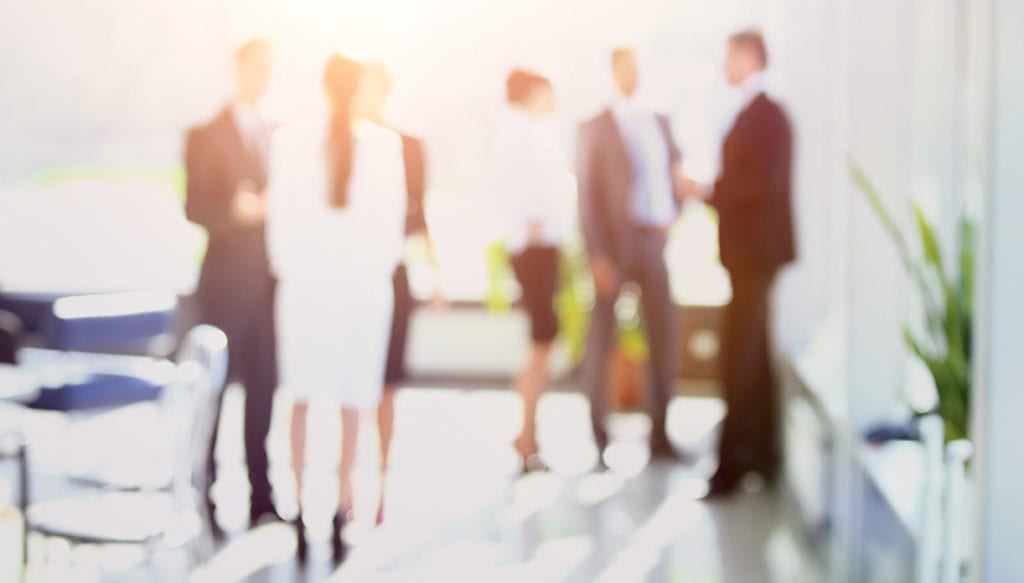 blurred image of business people standing in office. business bac