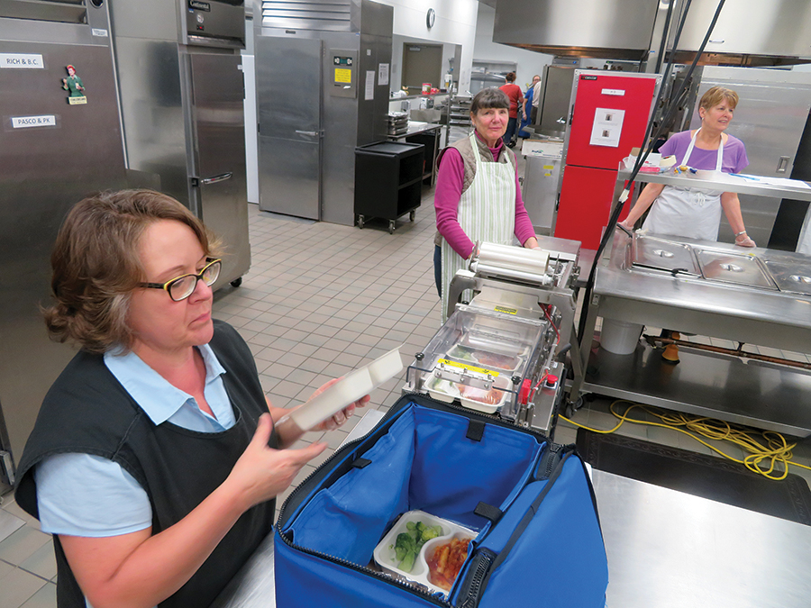 Mid-Columbia Meals on Wheels is canceling its annual fundraising breakfast scheduled for March 10 amid concerns about the continued statewide spread of coronavirus. Stephanie Burke, the packaging coordinator for Meals on Wheels, slides a pasta meal into an insulated tote to ready it for delivery. (File photo)
