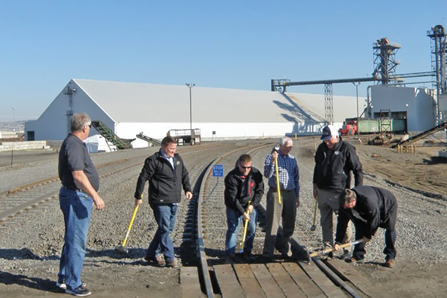 Officials with Central Washington Corn Processors pound in ceremonial rail spikes to celebrate the opening of their multimillion-dollar facility in this November 2016 file photo. The company is expanding its Richland footprint again this year. (File photo)