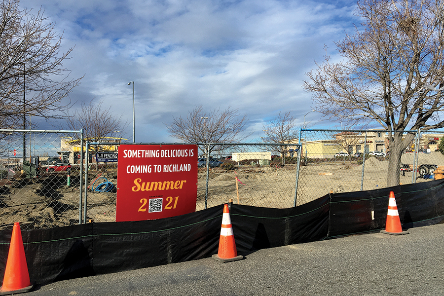 A sign encourages passersby to scan a QR code to find out what is under construction in the Richland Walmart parking lot at 2831 Duportail St. (Photo by Kristina Lord)