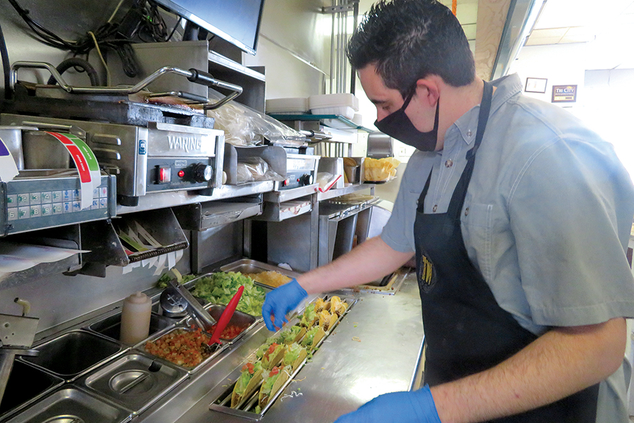 Keith Moon adds tomatoes to the line of tacos being prepared for the lunch crowd at Tumbleweeds at 894 Stevens Drive in Richland. Moon said his restaurant and crew have adapted to the turbulent year of the pandemic. (Photo by Kristina Lord)